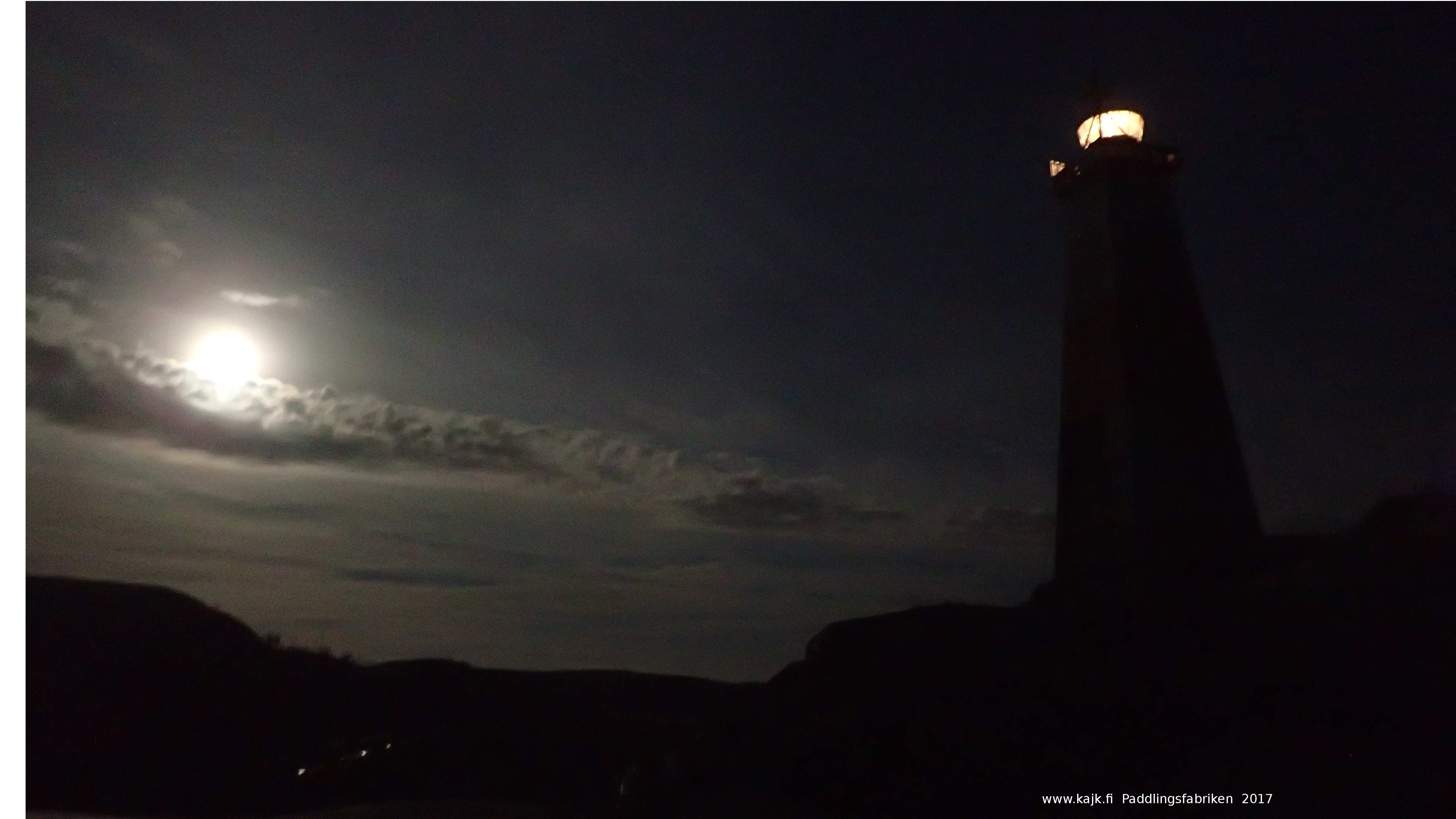 Jussarö lighthouse against a moonlit sky during one of the kayak tours